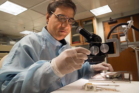 Using a binocular microscope, Dartmouth geochemist Mukul Sharma examines impact-derived spherules that he and his colleagues regard as evidence of a climate-altering meteor or comet impact 12,900 years ago. Photo: Eli Burakian