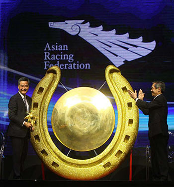 The Hon Leung Chun-ying, Chief Executive of the Hong Kong Special Administrative Region, rings the gong to mark the opening of the conference, as Dr Koji Sato, Chairman of the Asian Racing Federation, looks on at right.