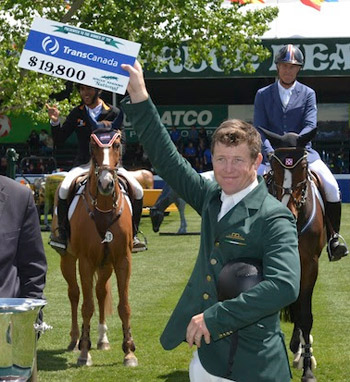 Shane Sweetnam raises his winning cheque.