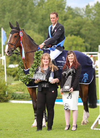 Trevor Breen is presented with the Boomerang Trophy for winning the 2014 Hickstead Derby with Adventure De Kannan. Presenting the award is Hickstead and Equestrian.com competition winner Bronte Patterson (right) and Lorraine Meadowcroft, CEO of Equestrian.com. © Samantha Lamb