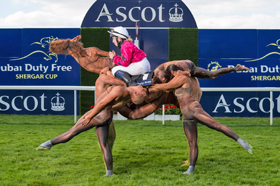 A team of ten acrobats form the shape of a racehorse crossing the winning post ridden by Stefanie Hofer.