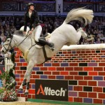 David Simpson jumps to victory on his mare Richi Rich to win the Alltech Christmas Puissance at Olympia, London.