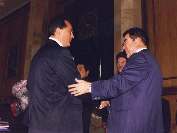 Geldy Kyarizov, left, is congratulated by former Turkmen president Sapurmurat Turkmenbashi.